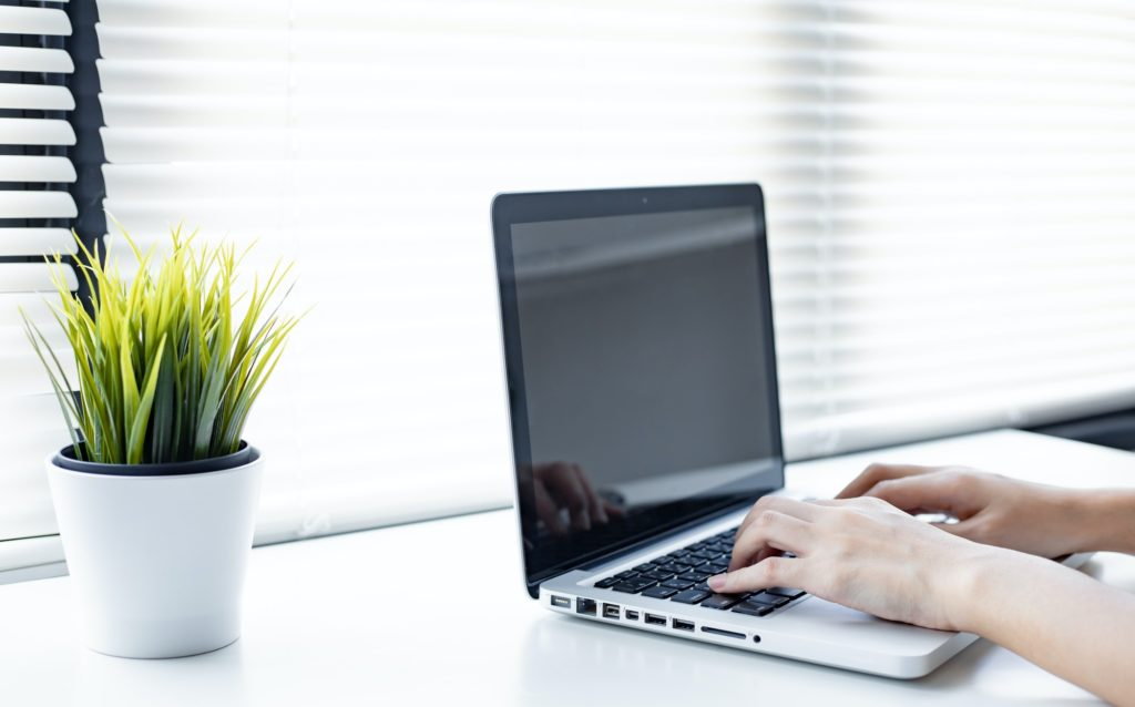 Young woman working from home by computer.